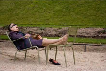 Woman asleep on two chairs