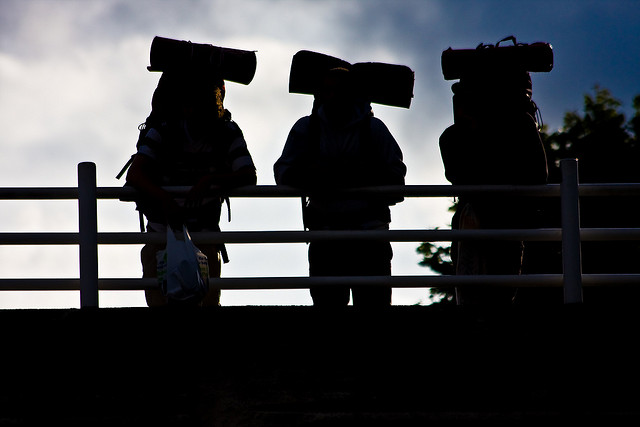 three backpackers in silhouette on bridge
