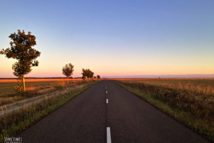 empty two-lane highway stretches into the pink and orange horizon