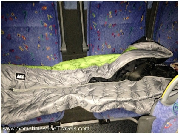 gray and green sleeping bag layed out in back seat of bus