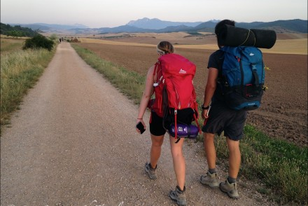 man and woman backpacking on road through fields at dawn