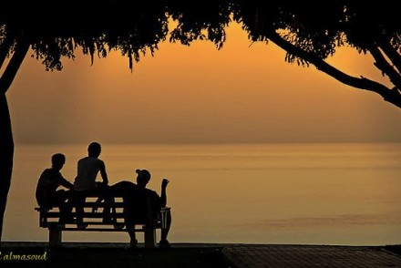 Silhouettes of three people on a bench at dusk