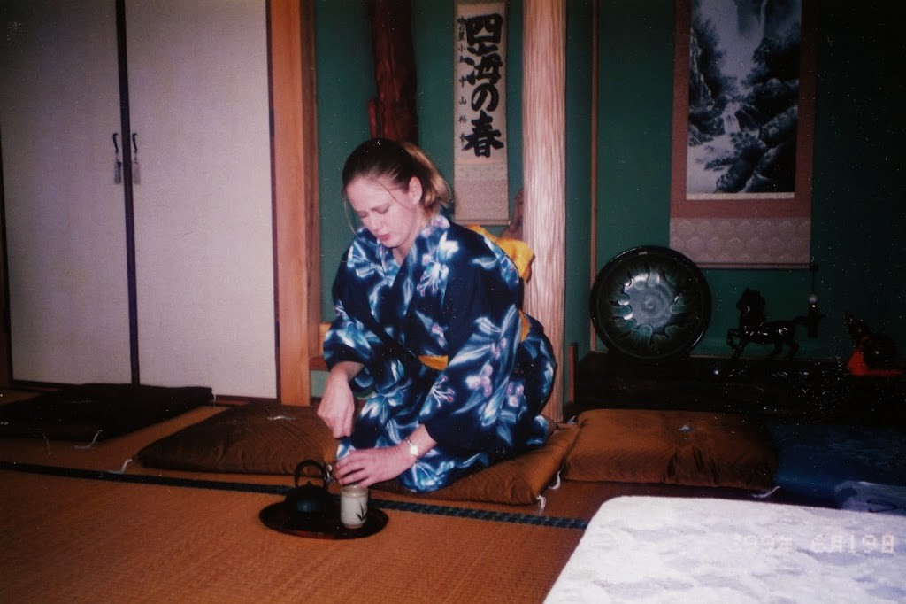 American woman in kimono doing tea ceremony