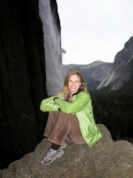 woman sitting on rock near waterfall in Yosemite