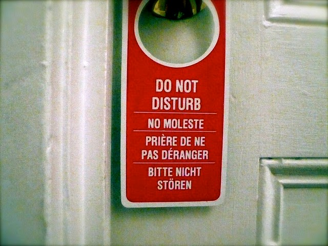 "A red sign on door knob that reads, ""Do not disturb""."