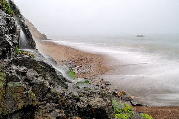 Waterfall on foggy beach