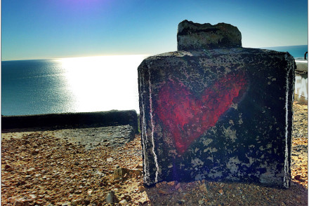 red heart on concrete block by ocean