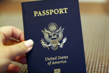 U.S. PASSPORT held in hand of woman with long nails