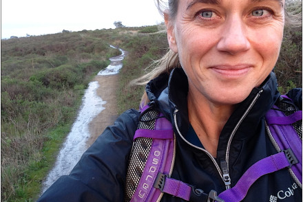 woman on wet trail wearing backpack
