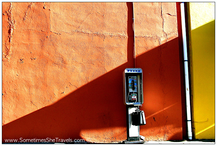 Old-fashioned phone booth in front of orange wall