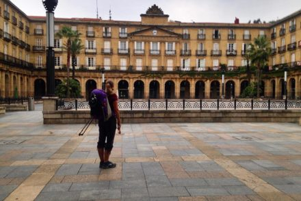 woman with backpack and hiking poles standing in the plaza of a European city