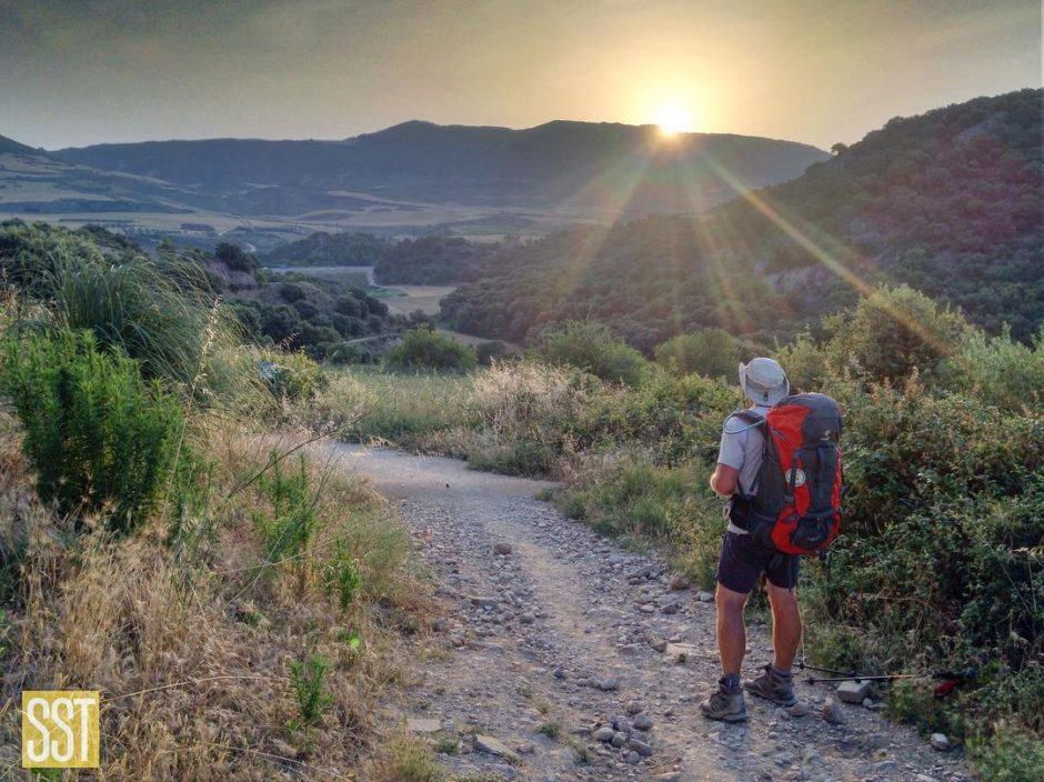 man wearing a red backpack standing on a trail looking at the sunrise