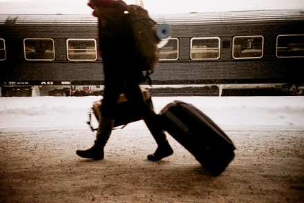 person in train station with suitcase, backpack, and satchel