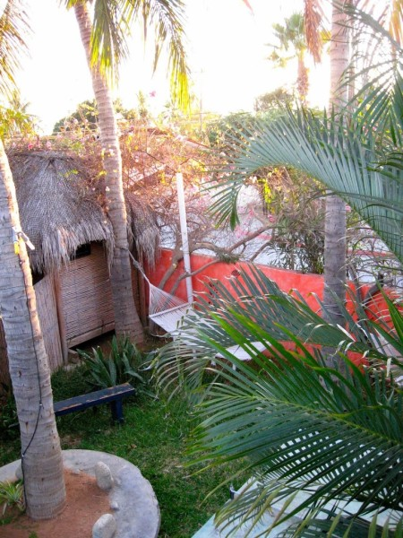 hammock next to orange wall and grass-roofed hut