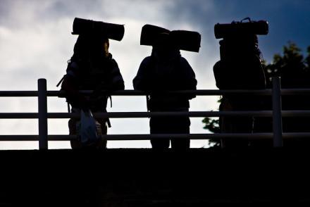 three backpackers in silhouette on bridge