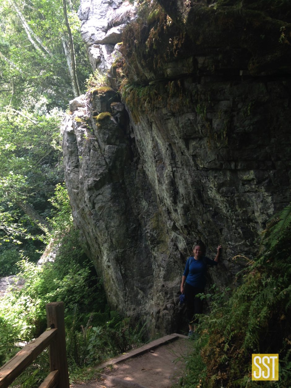 woman in blue shirt and black pants standing on trail next to giant rock