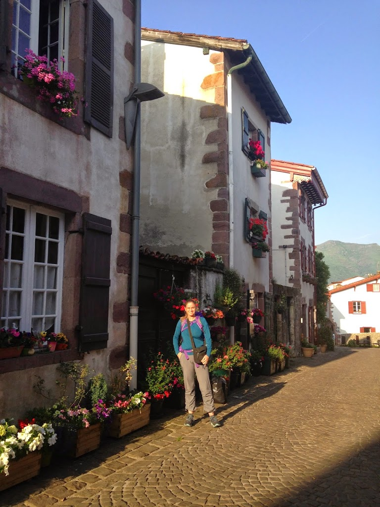 Woman in hiking clothes stands on cobblestone street next to basque houses with planters of bright flowers