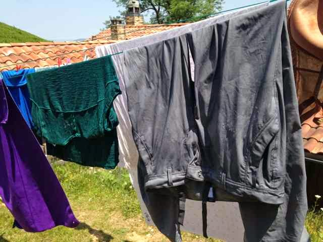 gray pants and teal shirt hanging on clothesline in sun