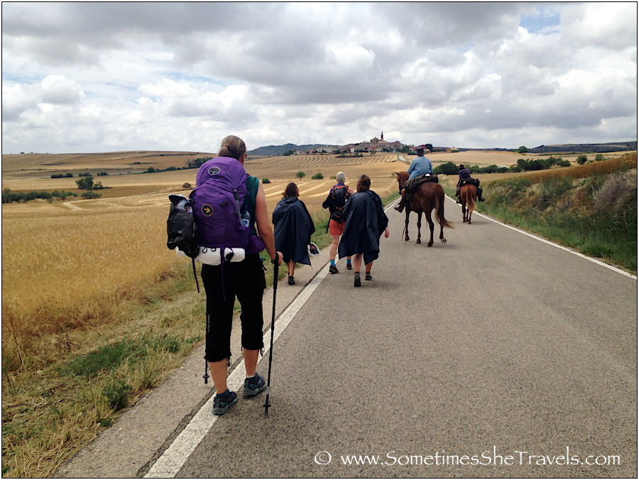 People with backpacks walking on paved road toward ancient hill town