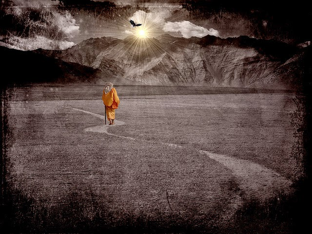 Man in orange robe walking on path to sun setting behind mountain