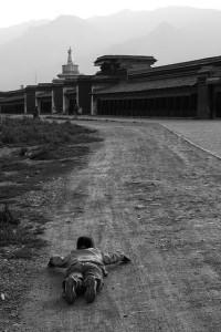 Man lying on dirt road near temple