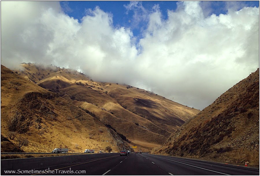Highway through mountains under cloudy sky