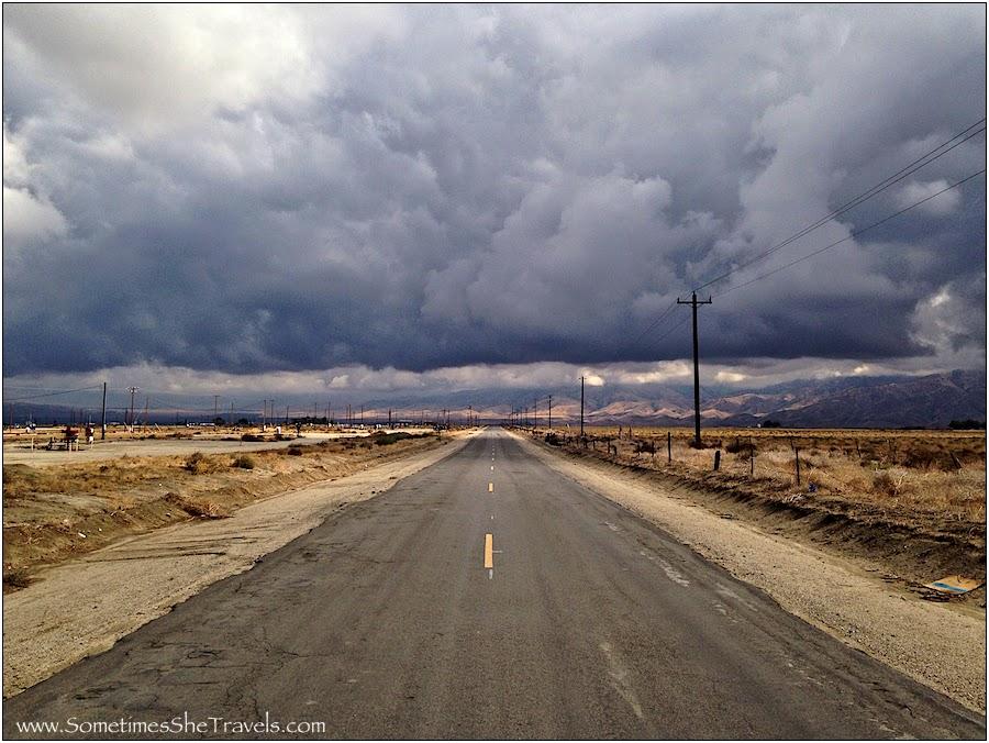 Road through desert toward giant clouds