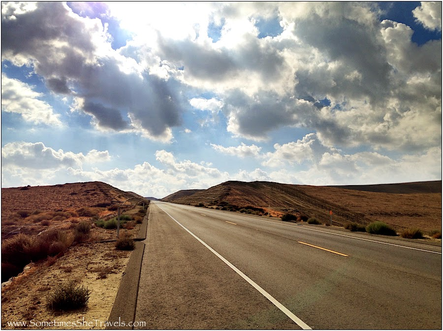 Road leading into desert mountains under partially cloudy sky