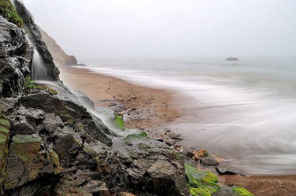 Waterfall on foggy beach