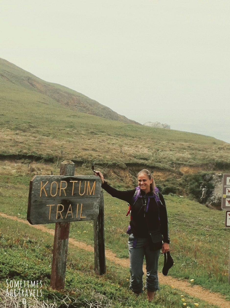 "woman wearing backpack stands on a trail and leans against a wooden sign that says ""Kortum Trail"""