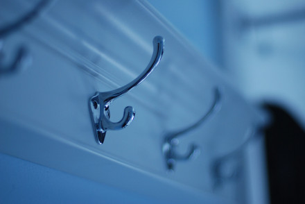 three metal shower hooks on wall