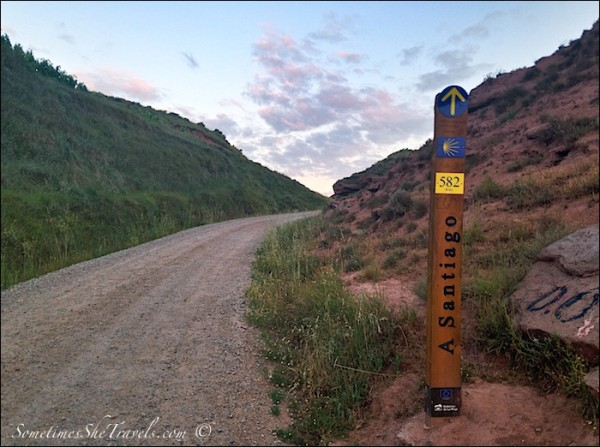 sign to Santiago next to dirt road at sunrise