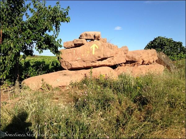 camino de santiago yellow arrow on red rocks