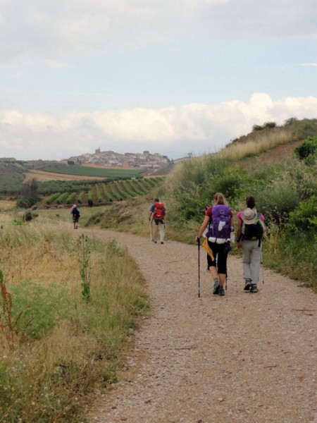 two women with backpacks walking on a trail toward a hill town