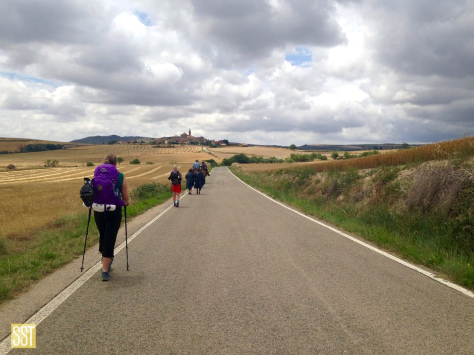 People with large backpacks walking on a road through cultivated fields toward a village on a hill under a cloudy sky