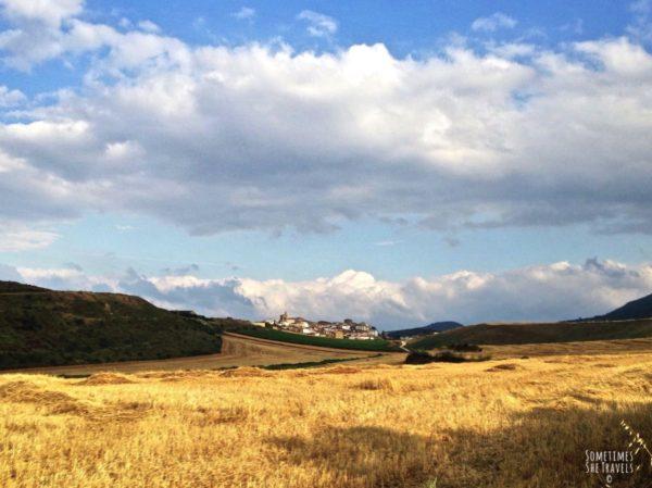 view of a hillside town in Spain across a field of grain