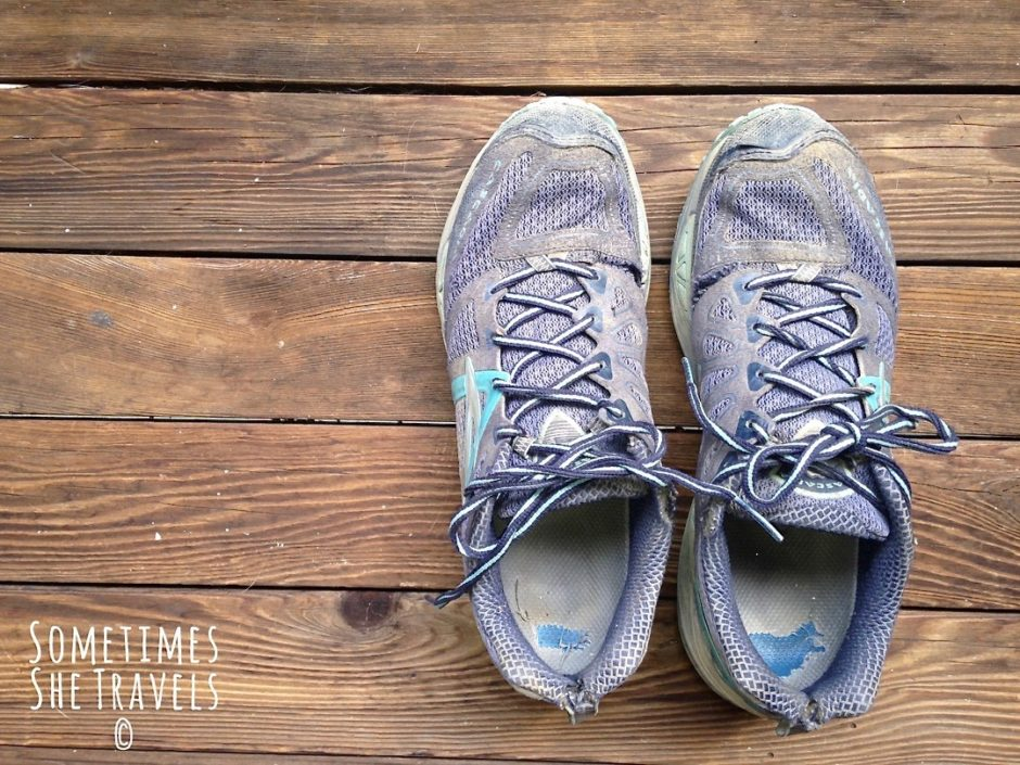 beat up blue running shoes on wooden deck