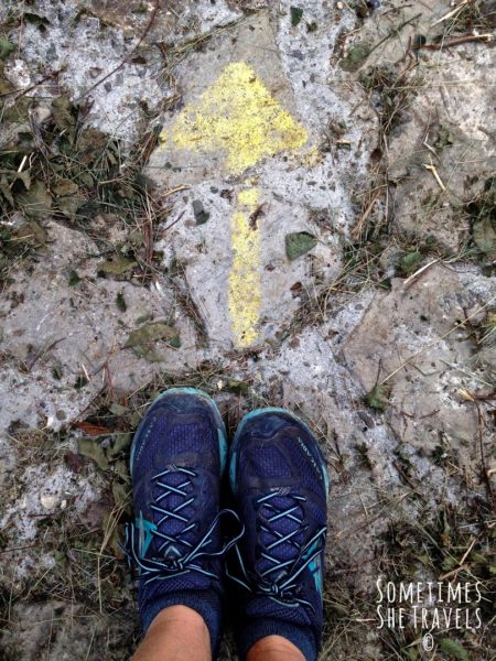 Person's feet in blue running shoes behind a yellow arrow on rocks pointing north